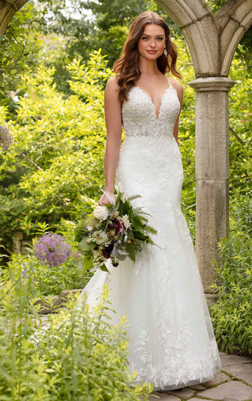 Bride wearing fit and flare wedding gown, and holding bouquet