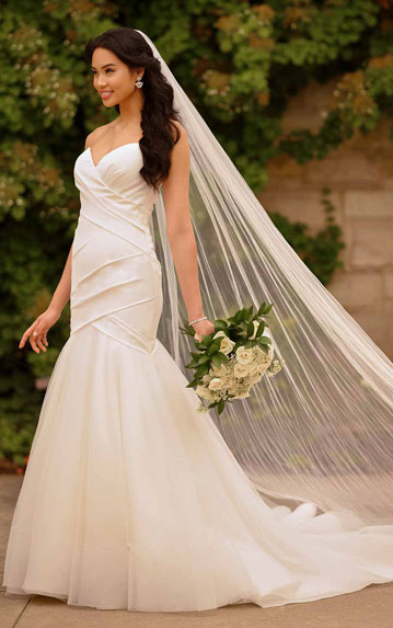 Bride wearing modern fit-and-flare wedding gown with pleats