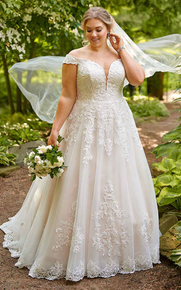 Plus size bride wearing traditional ball gown with veil