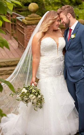 Plus-size bride wearing fit-and-flare wedding dress with veil, standing with groom