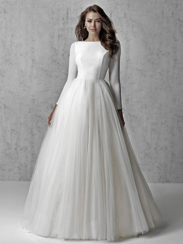 Ball gown wedding dress with long sleeves, standing in front of gray background