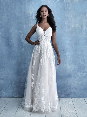 Bride wearing lace boho A-line wedding dress, standing against blue background