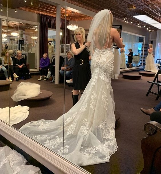 Bride trying on dress with bridal stylist in bridal shop