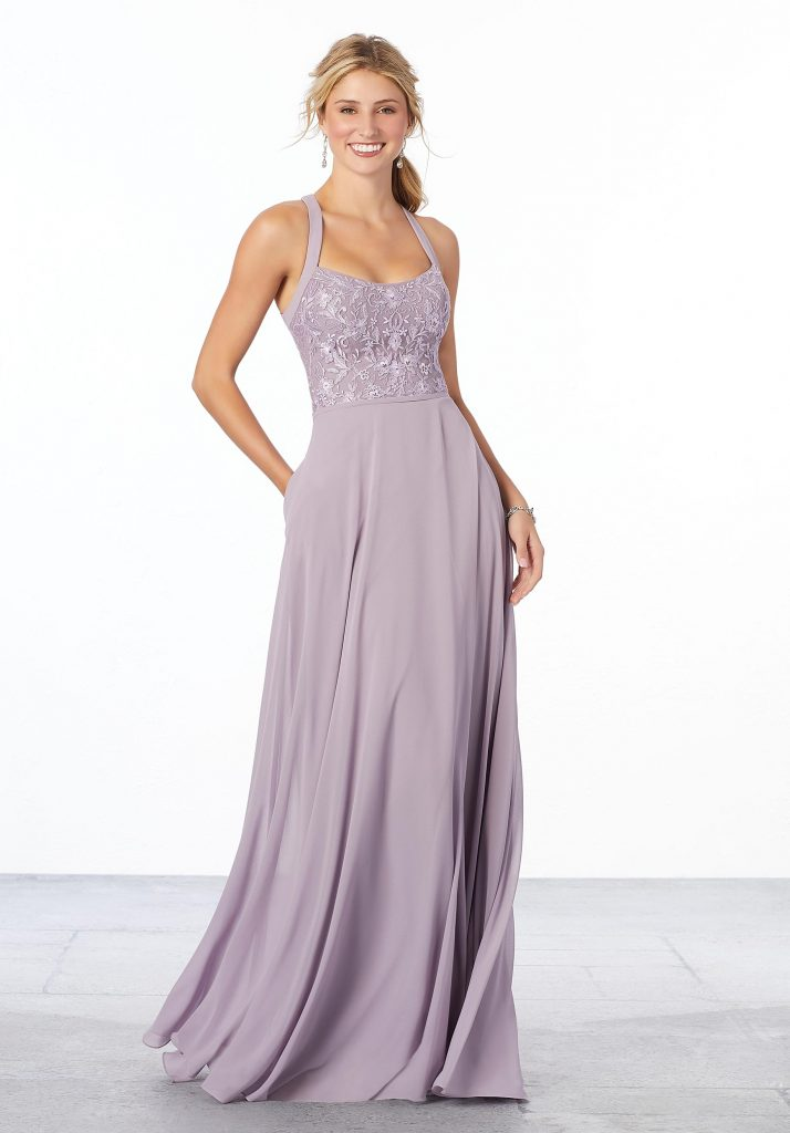 Young woman wearing feminine chiffon lilac bridesmaid dress with a floral detail embroidered bodice, flowing A-line skirt, and keyhole back
