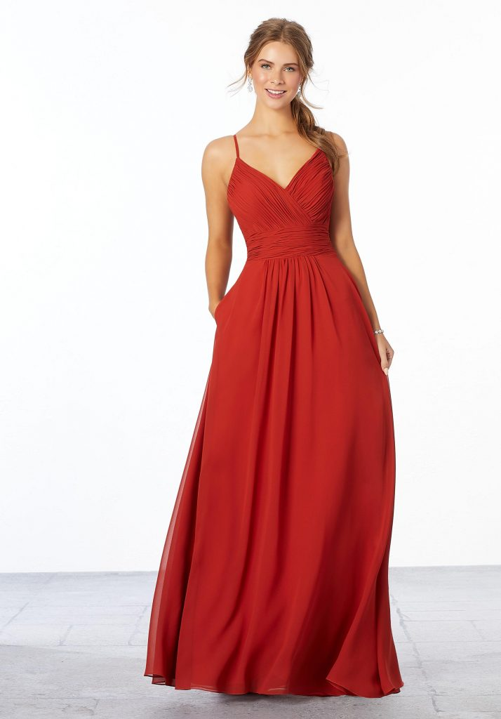 Young woman wearing A-line cinnamon chiffon bridesmaid dress with a ruched, v-neck bodice, and ruched waistband