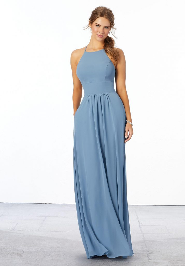 Young woman wearing simple slate blue A-line chiffon bridesmaid dress with high halter neckline and cinched waist