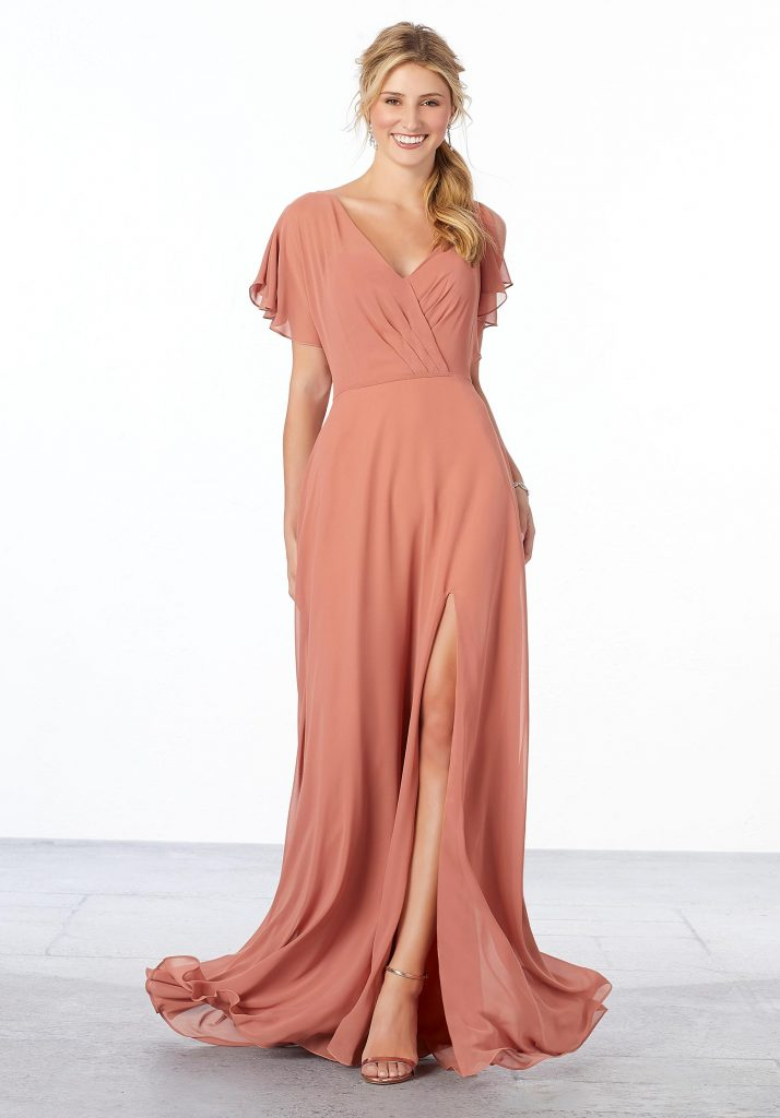 Young woman wearing flowing spice-colored A-line chiffon bridesmaid dress featuring a surplice bodice with flutter sleeves, v-back, and front slit