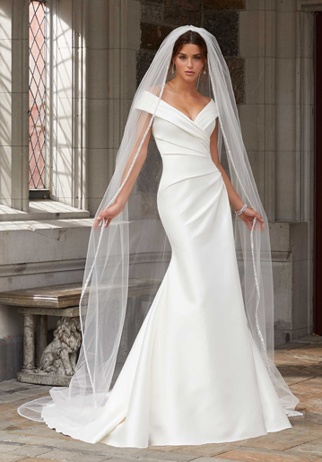 Modern bride wearing fit-and-flare wedding dress with off-the-shoulder cap sleeves and veil from Mori Lee