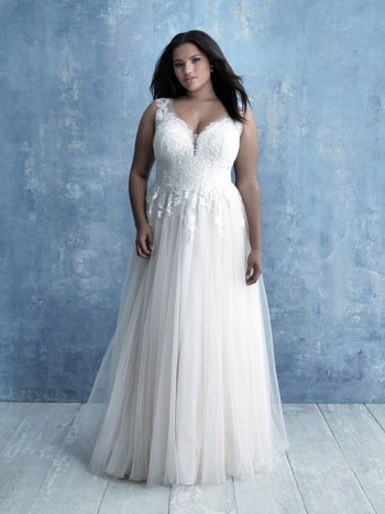 Plus-size bride wearing A-line wedding dress, standing against blue background