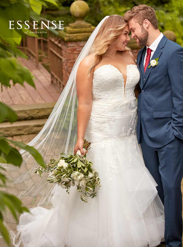 Plus-size bride wearing romantic fit and flare wedding dress with veil
