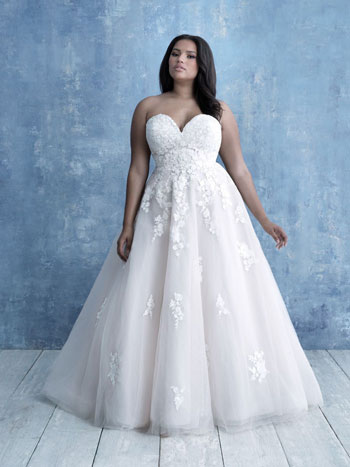 Plus-size bride wearing strapless ball gown wedding dress, standing against blue background