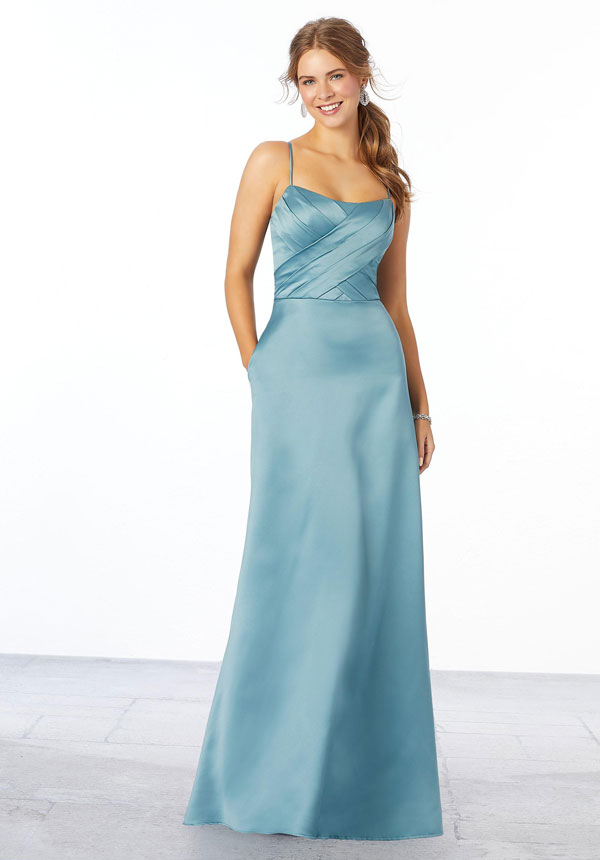 Young woman wearing deep sea blue, sleek satin A-line bridesmaid dress with a pleated bodice