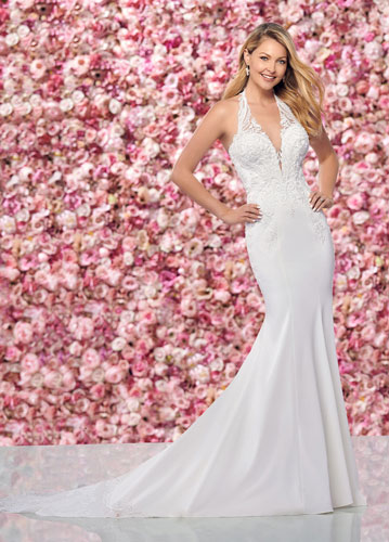 Bride standing in front of flower wall, wearing sleeveless lace fit and flare bridal gown with halter neck