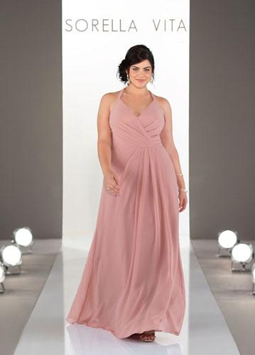 lus-size model on runway wearing rose-colored long bridesmaids dress with halter neck