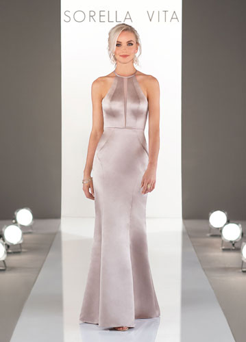 Model on runway wearing taupe-color long satin bridesmaids dress with hater neck
