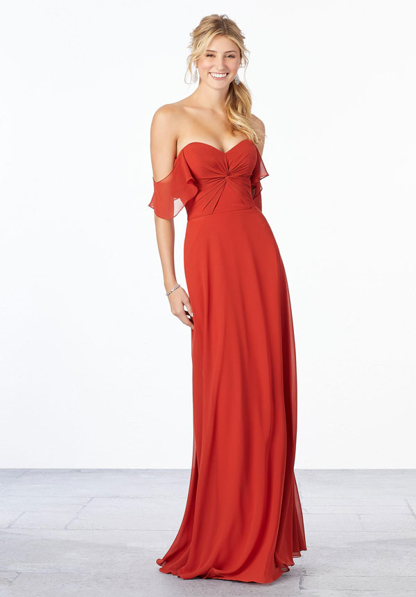 Young woman wearing cinnamon chiffon A-line bridesmaid dress with ruched bodice, sweetheart neckline, and off-the-shoulder flutter sleeves