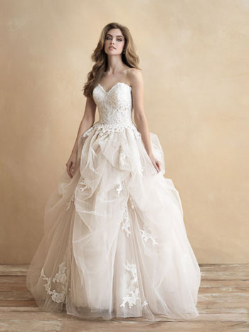 Bride wearing princess ballgown wedding dress, standing against tan background