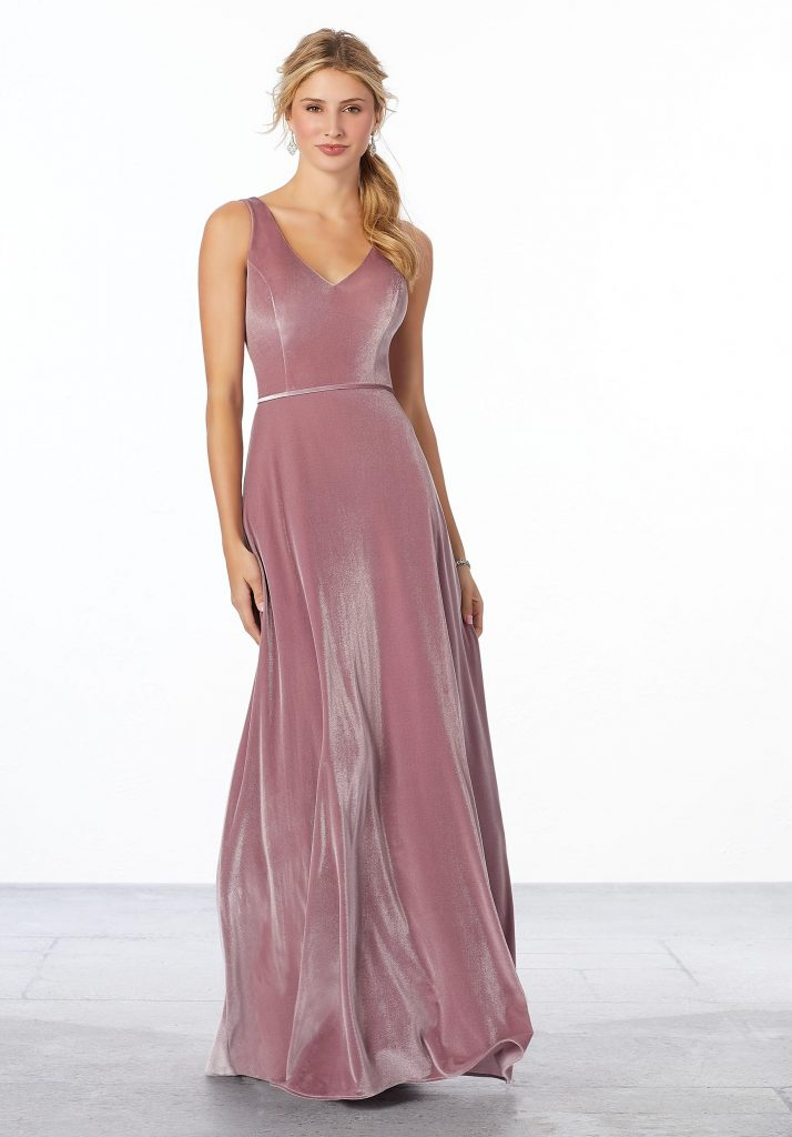 Young woman wearing desert rose stretch Velvet A-line bridesmaid dress with a v-neckline, v-back, and matching velvet waistband