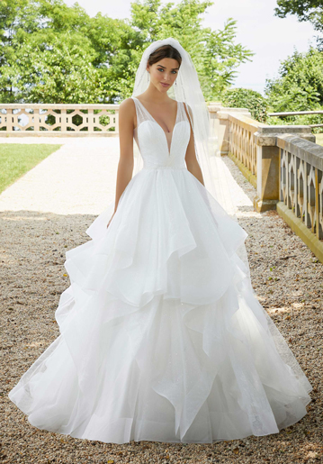 Bride standing outside wearing sleeveless v-neck ball gown wedding dress with tiered skirt