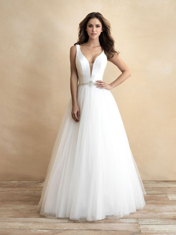 Bride wearing ballgown wedding dress with v-neck, standing against tan background