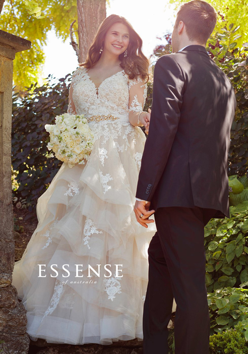 Beautiful plus-size bride wearing Essense of Australia wedding dress with long lace sleeves