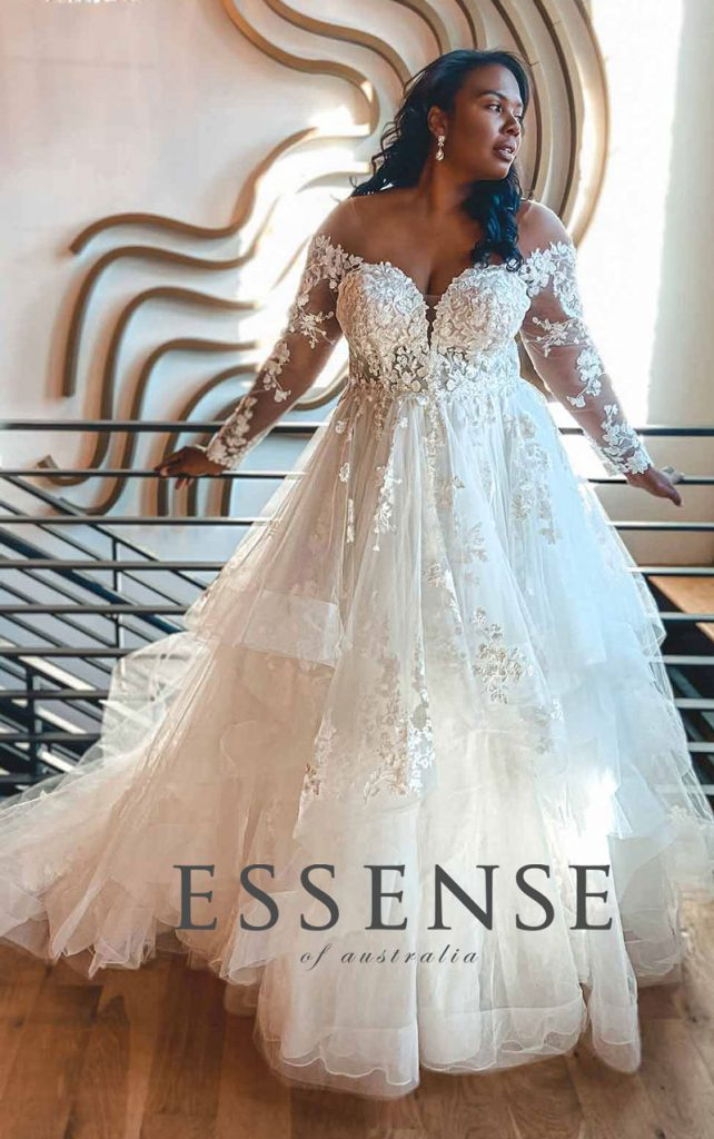 Romantic plus-size ballgown bridal gown with lace sleeves and tiered skirt