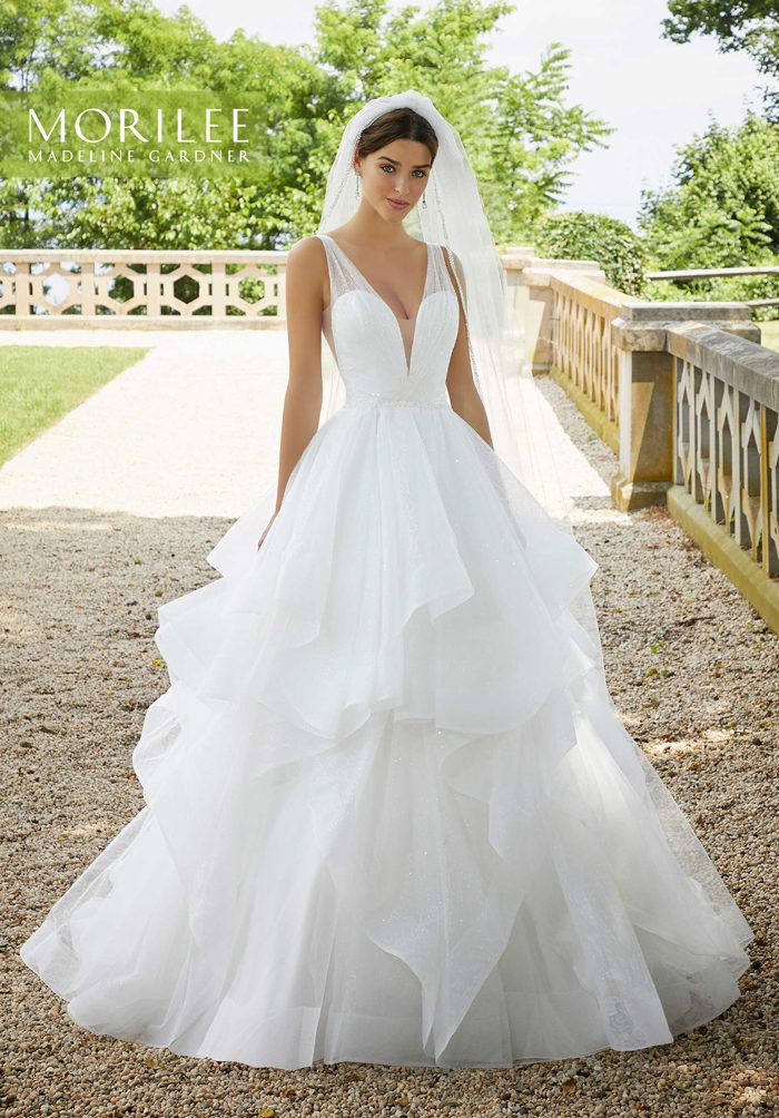 Bride outdoors wearing ballgown wedding dress with tiered skirt and veil