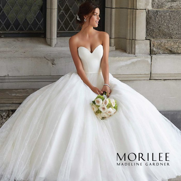 Bride sitting on concrete bench, wearing strapless ball gown