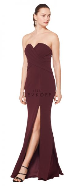 Young woman wearing strapless burgundy bridesmaids dress with leg slit